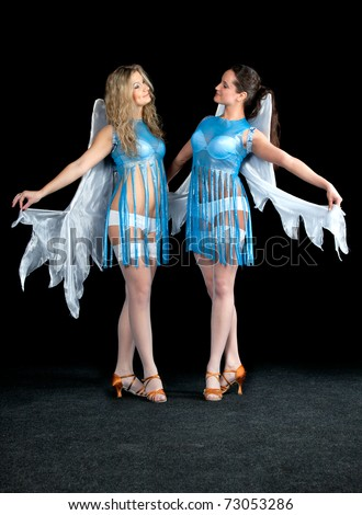 Two women in a blue dress with angel wings dance on a black background