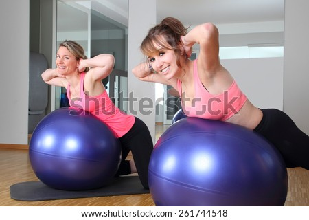 Two women in a fitness center together on a Fitness Ball - stock photo