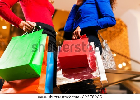 Two women in a shopping mall with colorful bags simply having fun - stock photo