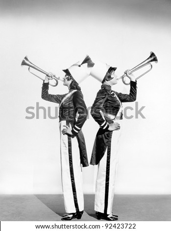 Two women in a toy soldier uniforms with trumpets - stock photo