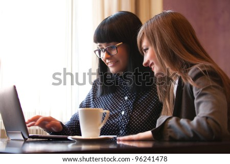 two women in cafe look in netbook and smile - stock photo