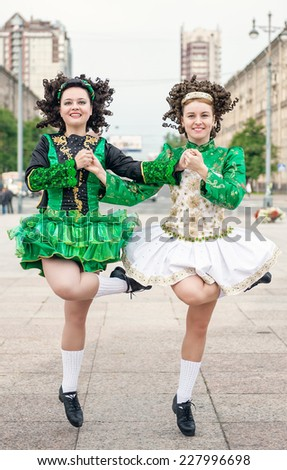 Two women in irish dance dresses and wig dancing