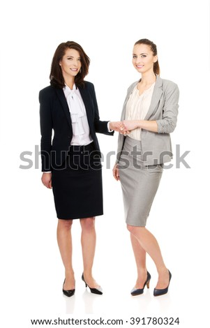 Two women in office outfits giving handshake. - stock photo