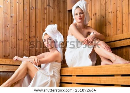 Two Women in sauna of wellness spa relaxing , enjoying an infusion  - stock photo