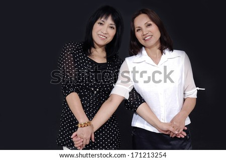 Two women in studio playing and smiling - stock photo
