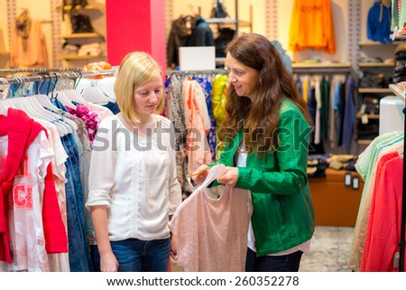 two women in the clothes shop looking for outfit - stock photo