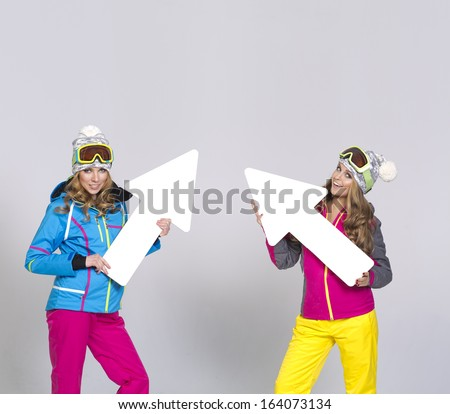 Two women in warm clothes with arrows