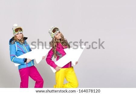 Two women in warm clothes with arrows - stock photo