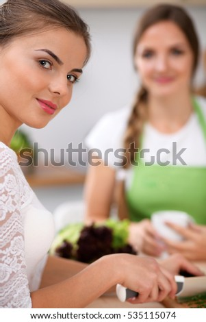 Two women is  cooking in a kitchen. Friends having a pleasure talk while preparing and tasting salad. Friends Chef Cook concept