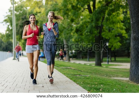 Two women jogging in park and listening to music - stock photo