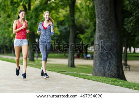 Two women jogging in park and listening to music