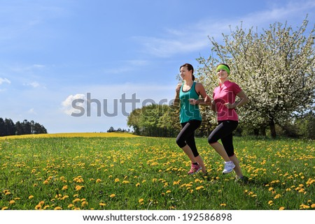 two women jogging through fields at the springtime - stock photo