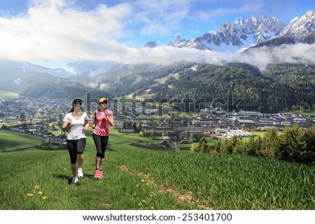 two women jogging through fields at the springtime
