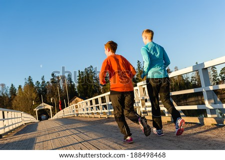Two women jogging together along the bridge at sunrise - stock photo