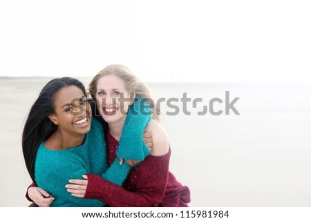 Two women laughing and smiling outdoors - stock photo