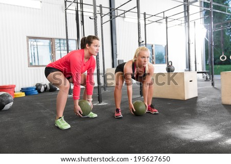Two women lifts crossfit slam balls - stock photo