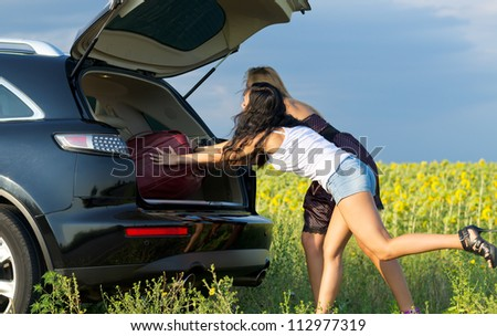 Two women loading luggage into the back of an estate vehicle parked alongside the road in the countryside near a field of sunflowers