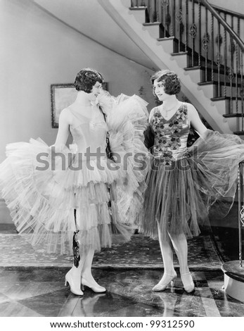 Two women looking at each others dresses - stock photo
