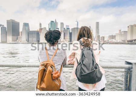 Two women looking at New York skyline - Multiethnic girls leaning on a railing and watching at cityscape - stock photo