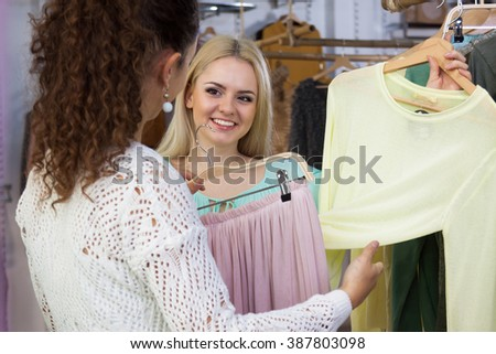 Two women looking for new garments at the store - stock photo