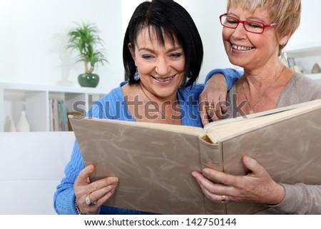 Two women looking through family photo album - stock photo