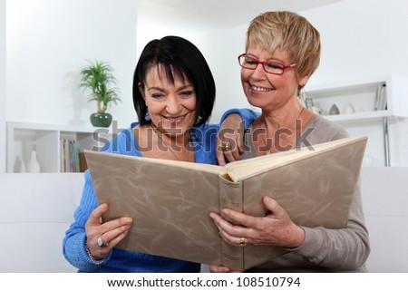 Two women looking through photo album - stock photo