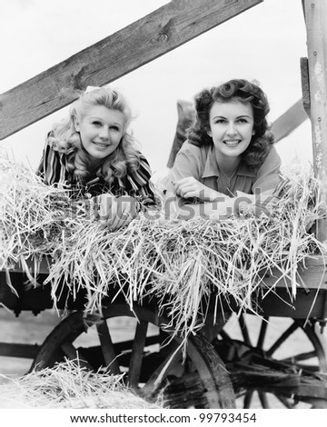 Two women lying in a wagon of hay with their legs in the air - stock photo