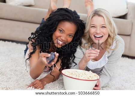 Two women lying on the ground with popcorn are smiling at the camera nd holding a TV remote - stock photo