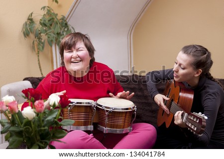 Two women make a music therapy and having fun - stock photo