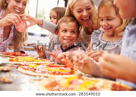 Two women making pizza with kids - stock photo
