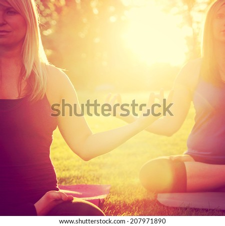 two women meditating in a yoga pose on the grass toned with a soft instagram like filter - stock photo