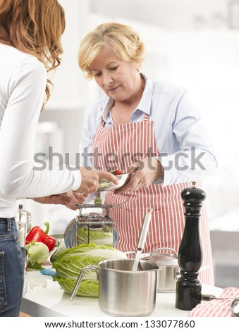 Two Women (Mother and Daughter) cooking Together In The Kitchen - stock photo