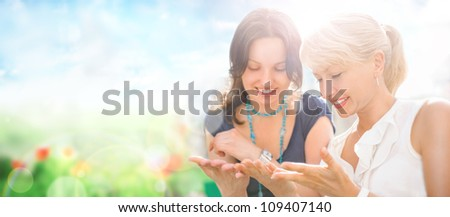 Two women mother and daughter sitting at park and having fun together. Lots of copyspace - stock photo