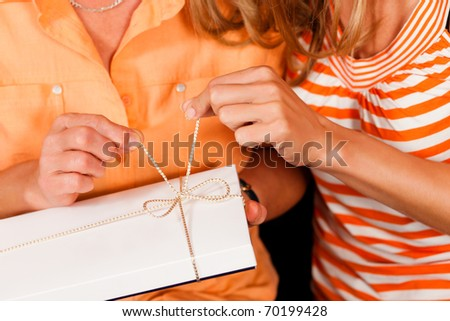 Two women � mother and daughter � sitting on a couch; the daughter has given her mother a gift - stock photo