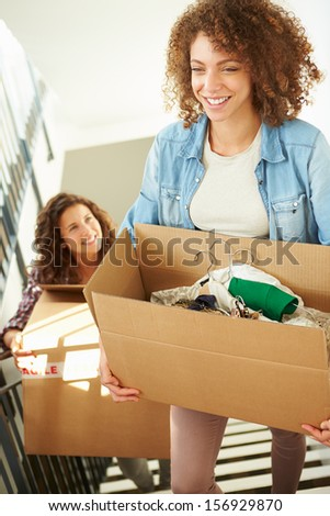 Two Women Moving Into New Home Carrying Box Upstairs - stock photo