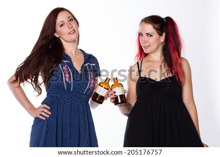 Two women offer a toast with brown bottles.