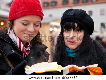 Two women on Christmas market eating crepes - a special kind of pancake - in front of a booth, it is cold - stock photo