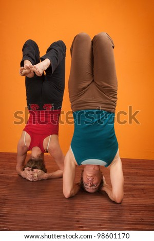 Two women perform Vrisikasana yoga posture over orange background - stock photo