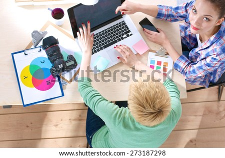 Two women photographer sitting on the desk with laptop - stock photo