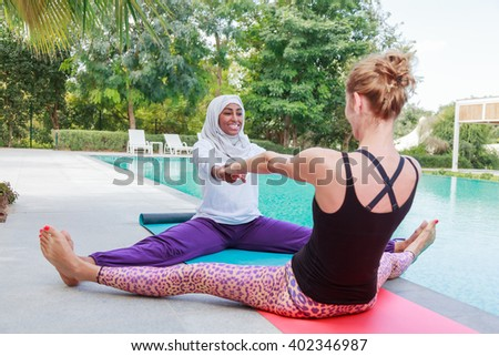 Two women practicing yoga outdoor in pair next to a swimming pool.