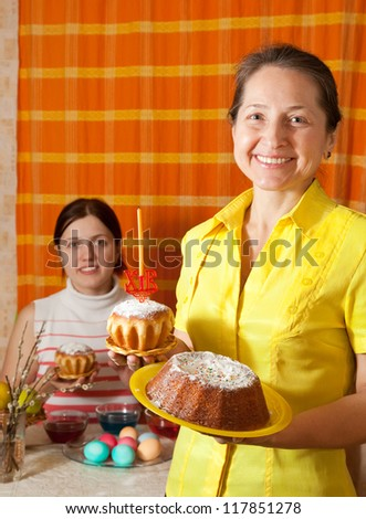 Two women preparing to  Easter holiday in home - stock photo