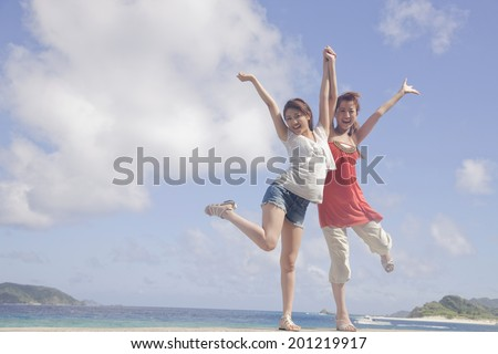 Two women raising their both hands on seaside