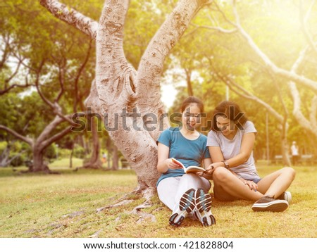 Two women reading a book together with happiness and relax feeling at the garden under sunlight with warm / soft color tone - stock photo