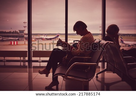 Two women reading the book while waiting plane in airport  - stock photo
