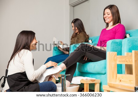 Two women relaxing and having a good time at a nail salon while getting a pedicure - stock photo
