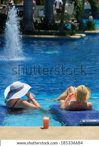 Two women relaxing in swimming pool with the cocktail glass (your text on top of the image) - stock photo