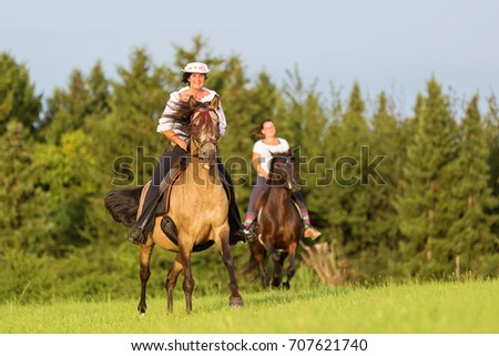 two women ride Andalusian horses in the fields