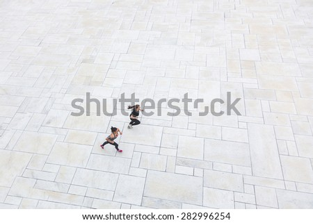 Two women running in the city, aerial view. They are wearing gray and black sportswear. - stock photo