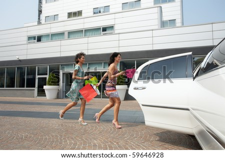 two women running into limousine with shopping bags. Horizontal shape, full length