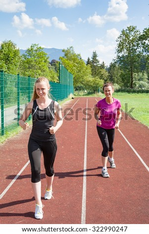 Two Women Running on Track Together and Having Friendly Race - Blond Woman Beating Brunette Woman in Track Race